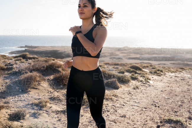 Close up of a woman running on a road near water stock photo