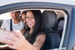 Side view of young people in a car taking a photo