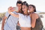 Three young people pouting as they take a slefie