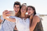 Three young people taking a selfie on the beach