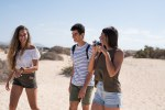 Three young people walking on a sandy beach