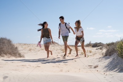 A boy and two girls are running down a sand dune