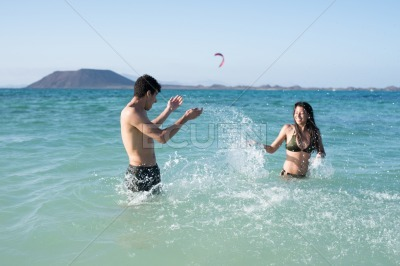Boy and girl splashing each other in the ocean