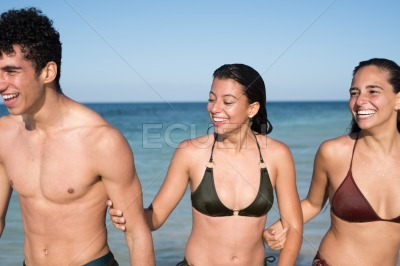 Close up of three young people emerging from sea