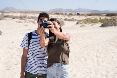 Couple take a photo of themselves at the beach
