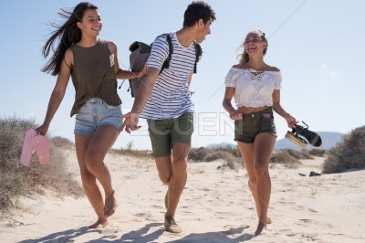 Girl hold a boys arm as they run along the beach