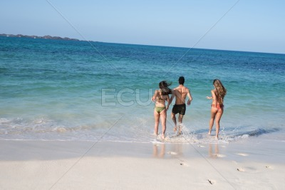Group of young people walking into the ocean