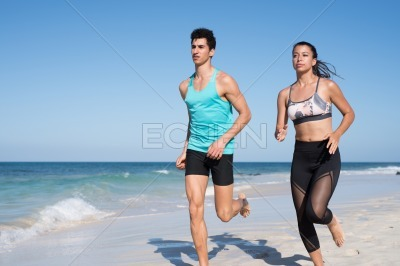 Man and woman running along the seashore