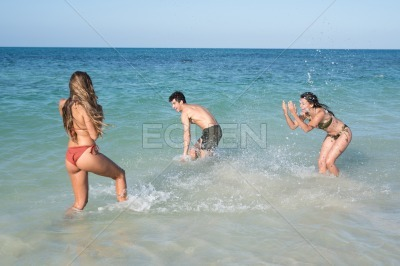Three attractive young people playing in the sea