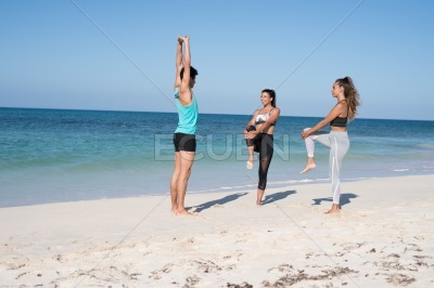 Three young people exercising on the beach
