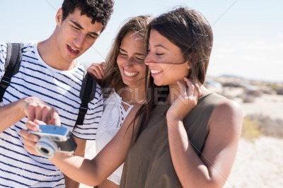 Three young people looking at the back of a camera