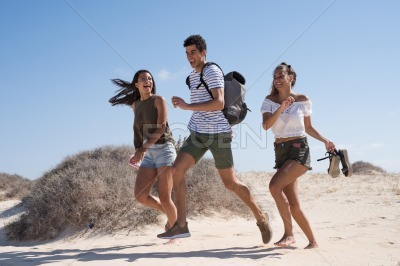 Three young people running and laughing