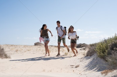 Three young people running on the beach