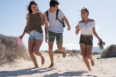 Three young people running on the sand