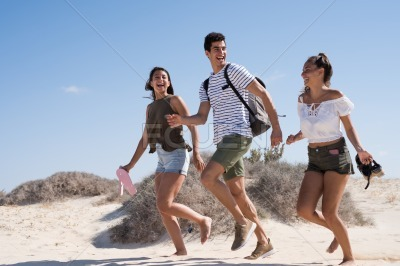 Three young people running together on the sand
