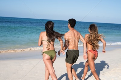 Three young people running towards the ocean