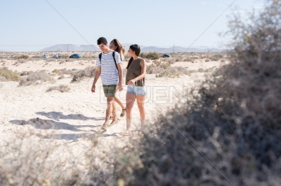 Three young people walking on a beach