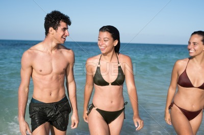 Three young people walking out of the ocean
