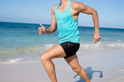 Torso shot of a young man running on the beach