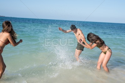 Two girls and a boy are playing in the waves