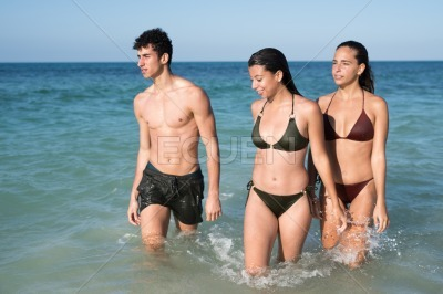 Two girls and a boy in swim wear are wet