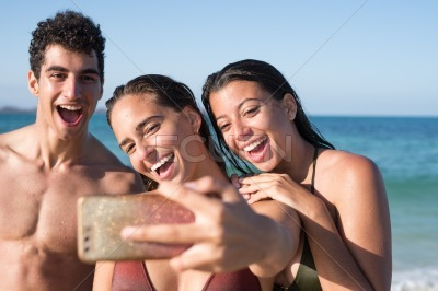 Two girls and a boy laughing at the camera