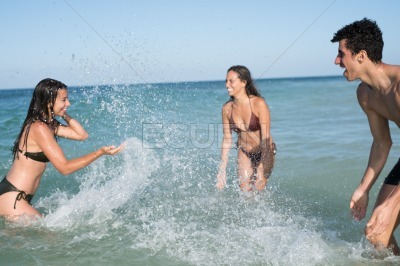 Two girls and a boy play and laugh in the sea