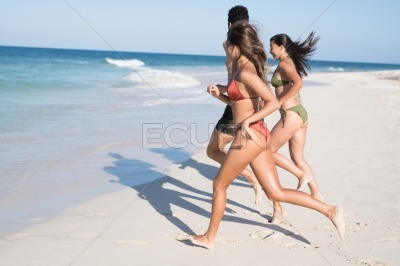 Two girls and a boy running by the breakwater