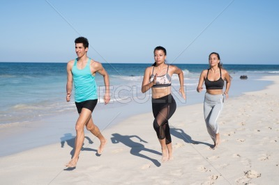 Two girls and a boy running on the beach