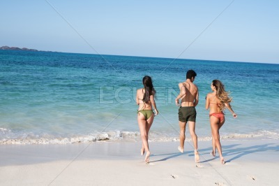 Two girls and a boy running towards the ocean
