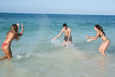 Two girls are splashing a boy in the waves
