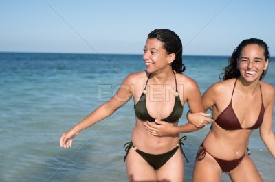 Two girls arm in arm on the beach