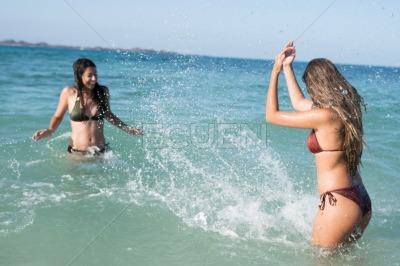 Two girls splashing each other in the waves