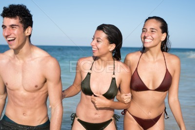 Two young girls and a boy are laughing by the sea