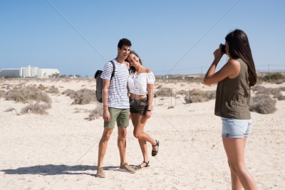 Woman taking a photo of a couple on a beach