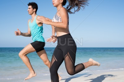 Young couple sprinting as they run on the beach