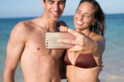 Young couple take a photo together on the beach