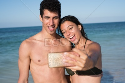 Young couple taking a photo together on the beach
