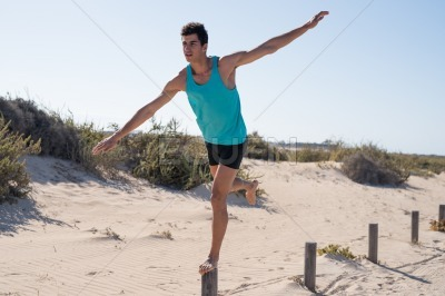 Young man standing on a pole with one leg