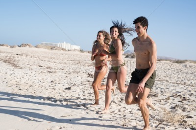 Young people running on the beach