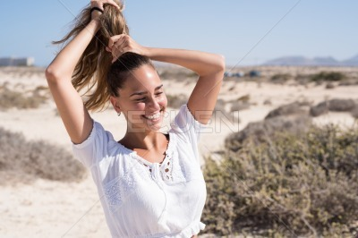 Young woman holding her hair in a pony tail
