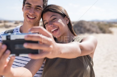 Young woman taking a photo of herself and a friend