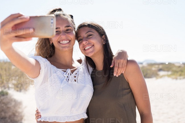 Girls smiling and laughing as they take a selfie