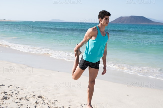 Man holds his leg behind him as he exercises stock photo