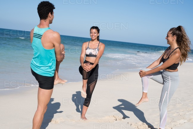 Three young people all holding their knees up