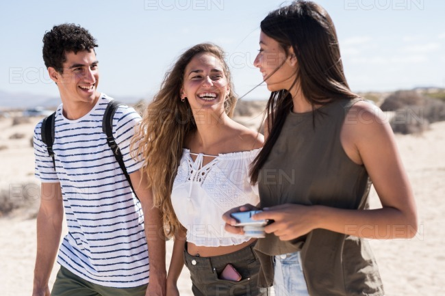 Three young people laughing and walking