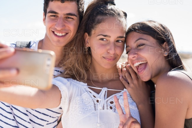 Three young people laughing at the camera