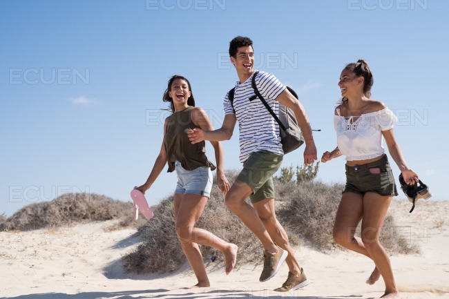 Three young people running together on the sand stock photo
