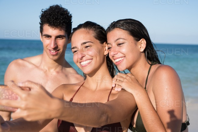 Three young people taking selfies on the beach stock photo