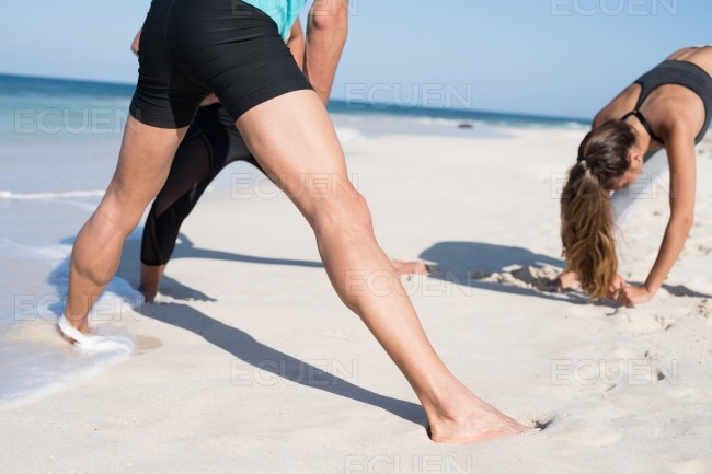 Two girls and a boy exercising on the beach stock photo